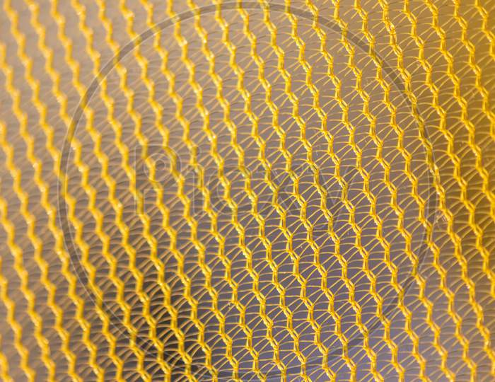Yellow mesh structure in close-up with backlight on shine morning shows abstract pattern of seamless material textured in golden light as graphical element for backdrop wallpaper and fabric macro