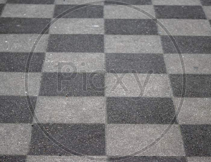 Chessboard pattern in waiting area on sidewalk pavement shows black and white checkerboard texture in rhombuses and geometric shapes background with black tiles and white tiles classic design surface