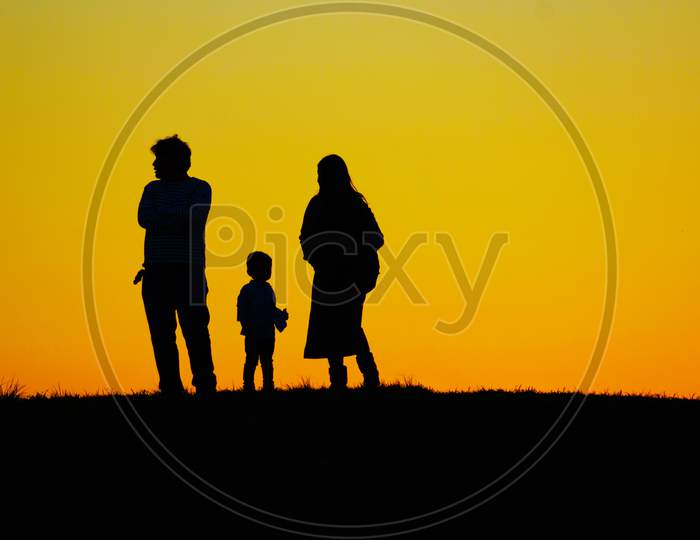 Family Standing On The Evening Of The Hill