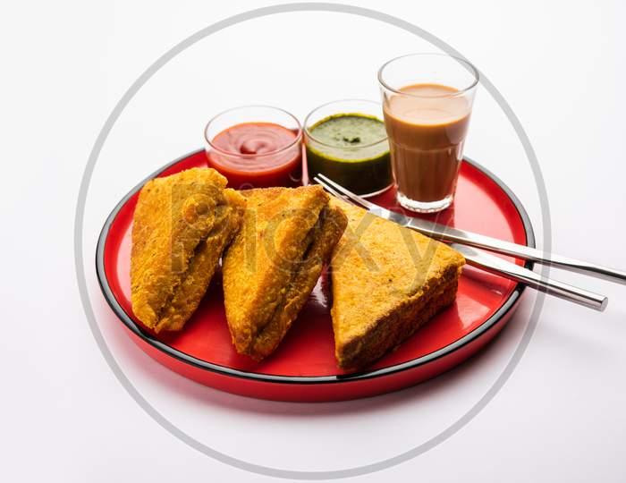 Sandwich Bread Pakora Or Triangle Shape Pakoda Served With Tomato Ketchup, Green Chutney, Popular Indian Tea-Time Snack