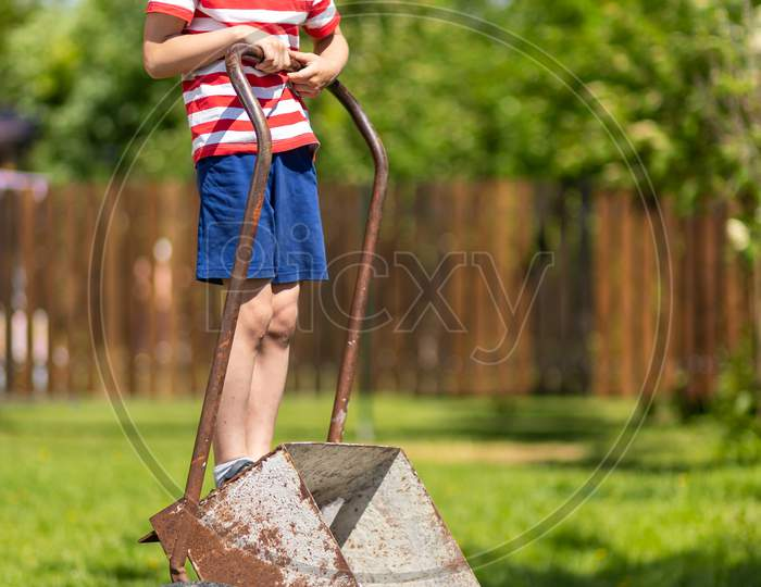 Cute Toddler Boy Playing With Big Old Wheelbarrow In Backyard In Outdoor Garden. Young Smiling Boy Playing With A Wheelbarrow In The Yard.