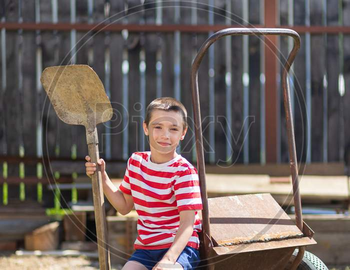 A Little Cheerful Boy Sits On A Garden Wheelbarrow And Holds A Shovel In His Hand In The Garden Of A Country House. Little Boy Helper Ready To Dig