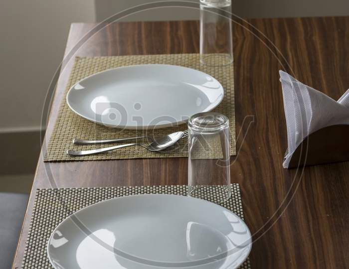Two Empty Plates With Spoon And Fork On A Wooden Table With Selective Focus.