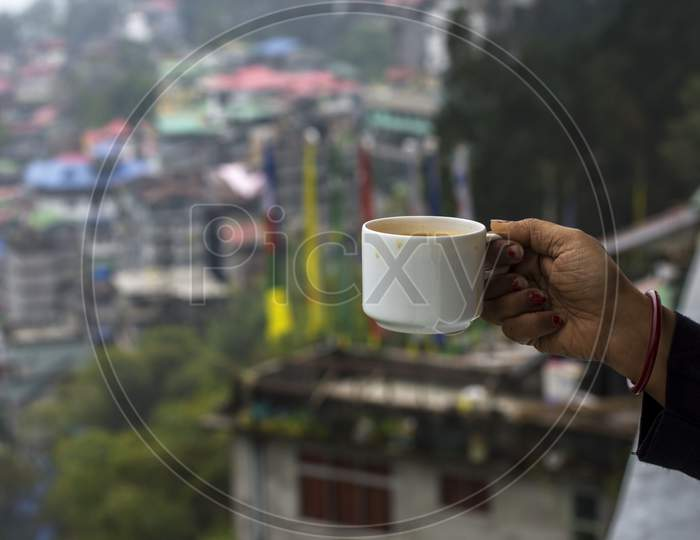 A Female Hand Enjoying Cup Of Tea With The View Of Gangtok City. Selective Focus.