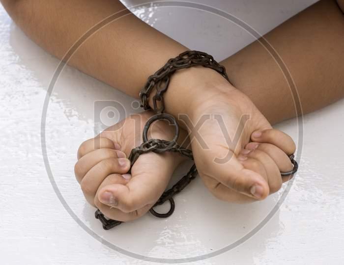 Hand Of A Child Tied Up With Chain On A White Background. Child Trafficking Concept.