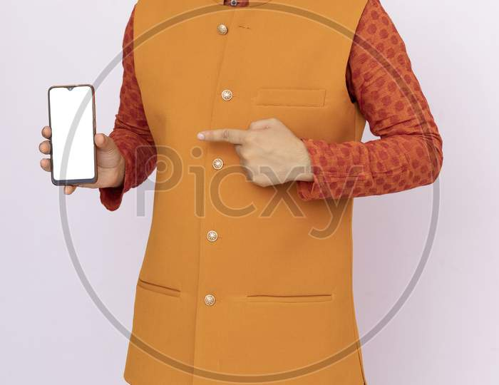 Portrait Of A Cheerful Young Man Wearing Ethnic Indian Traditional Clothing Isolated Background, Showing Blank Screen Mobile Phone.