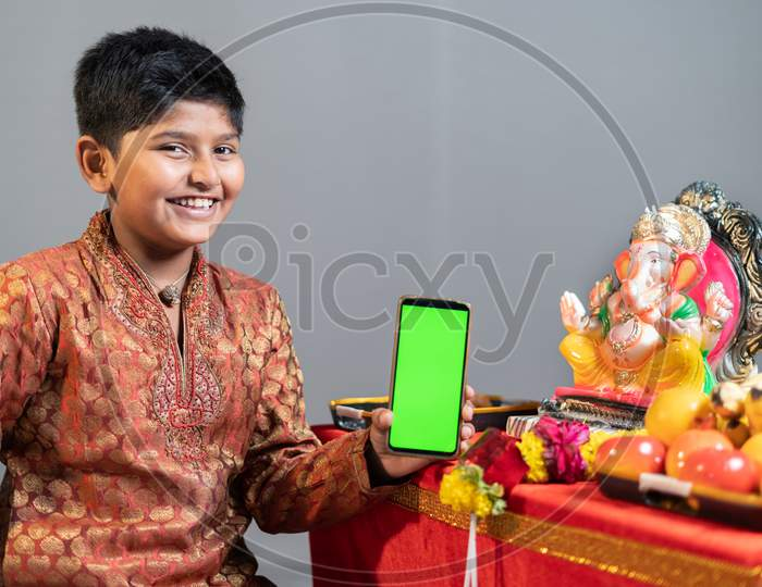 Studio Shot Of Happy Smiling Kid Holding Mobile Phone With Green Screen In Front Of Lord Ganesha Idol During Festival Celebrations.
