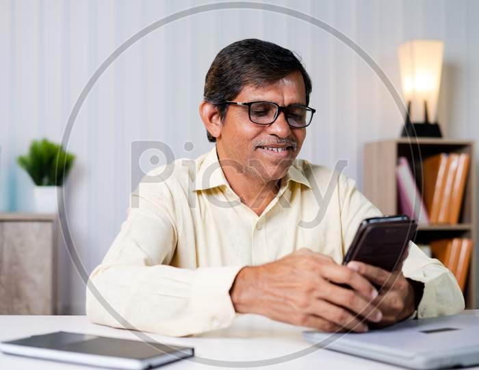 Middle Aged Businessman Smiling While Using Mobile Phone At Office - Concept Of Using Social Media, Internet, Checking Mails And Communication At Workplace