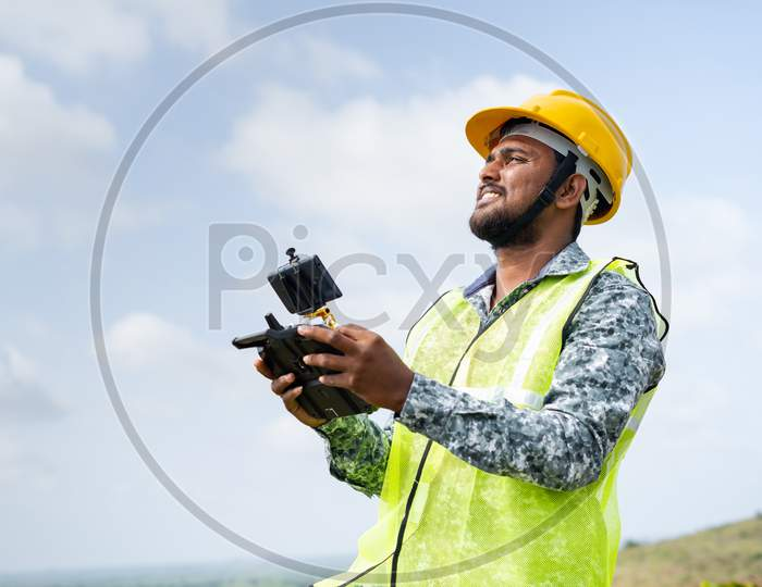 Drone Pilot With Safety Helmet Operating Drone Using Remote Controller - Concept Of Engineer Using Drone Technology To Survey Land.