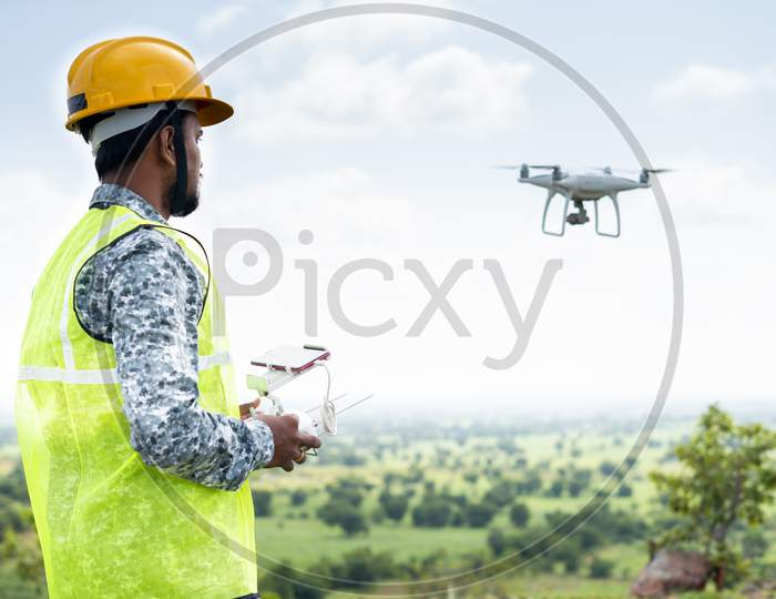 Pilot With Safety Hardhat Flying Drone Using Remote Controller - Concept Of Engineer Doing Aerial Survey Or Inspection Using Uav.